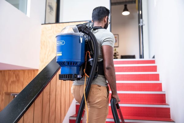 man walking up stairs with a pacvac vacuum cleaner