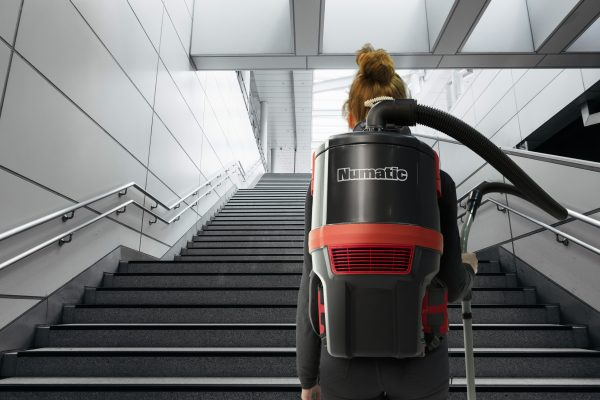 Woman walking up the stairs wearing a RSB150NX vacuum cleaner