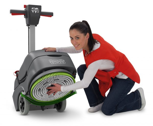 Woman fixing a green and white scrubbing brush onto a scrubber dryer model TTB1840NX