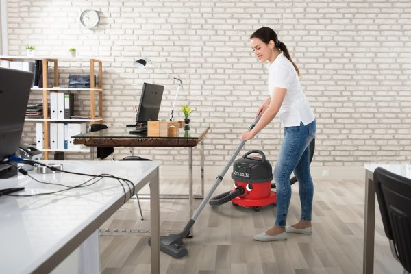 Cleaner vacuuming office with Numatic NBV240NX