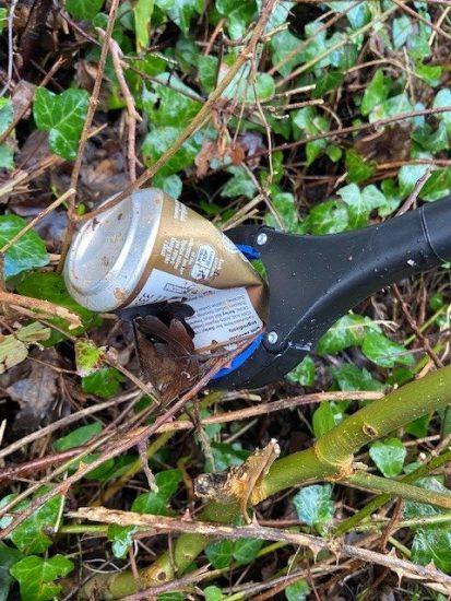 a litter picker grabbing a tin can